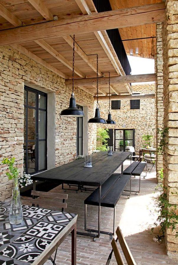 Terraza con pared de piedra y porche de madera