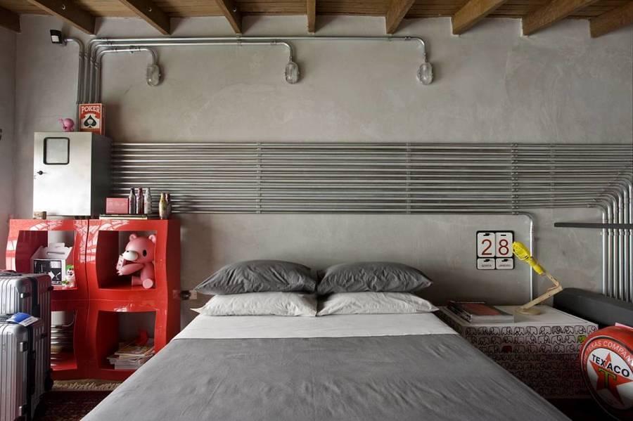 Recámara estilo industrial con tuberías a la vista en la pared