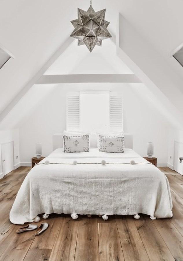 Recámara con textiles blancos y piso de madera