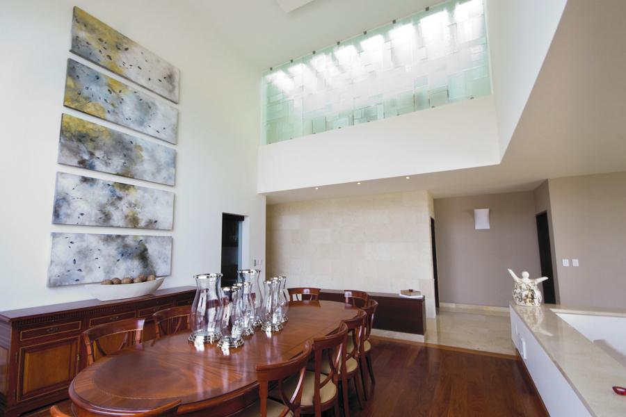 El comedor en doble altura, con vitral monocromático en el pasillo de planta alta