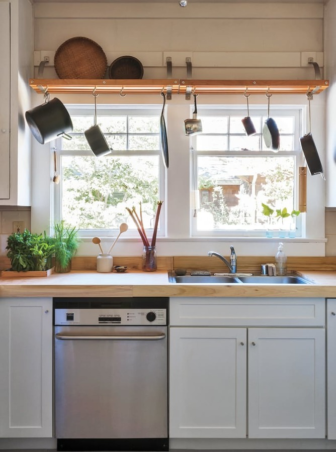 Cocina con barra de madera y utensilios colgando