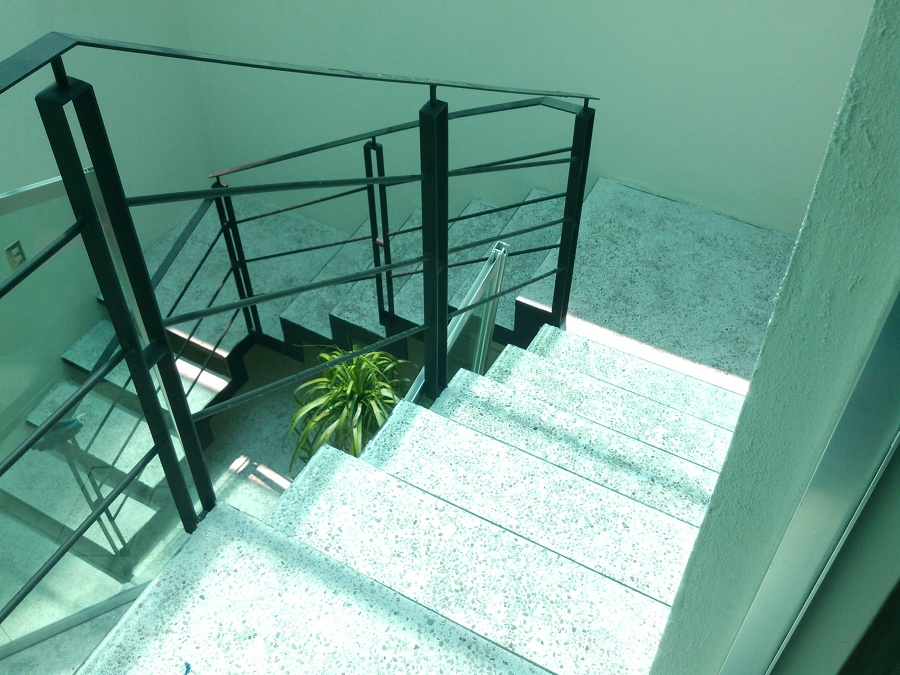 Escalera de servicio en herrería con huellas coladas de concreto con piedra piñon
