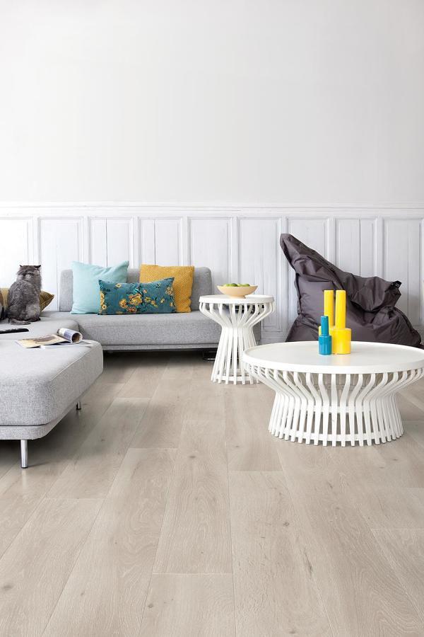 Sala con piso laminado y moldura blanca
