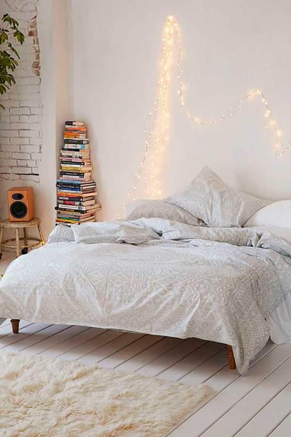 Recámara decorada con guirnalda de luces sobre la cama