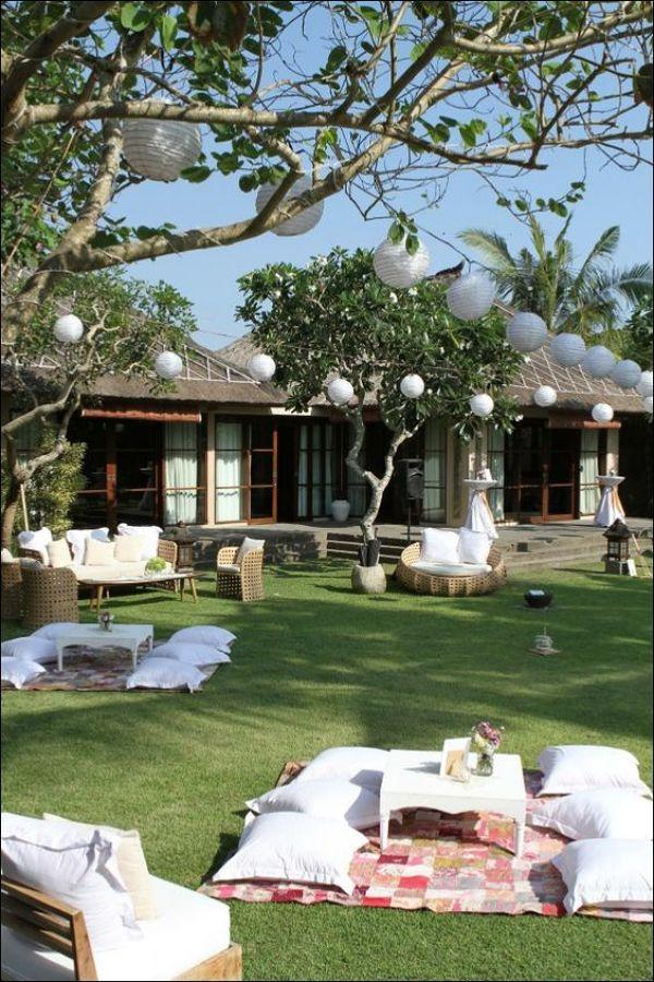 Jardín decorado con sillones, puff y alfombras