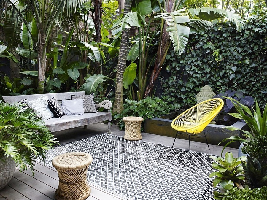 Jardín tropical con sillas y bancos