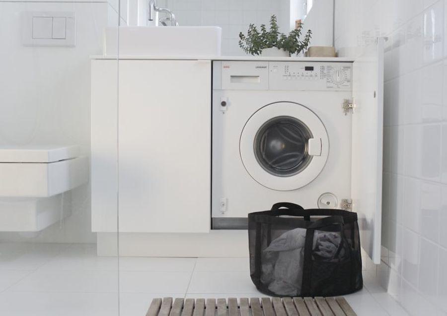 Lavadora oculta con paneles blancos