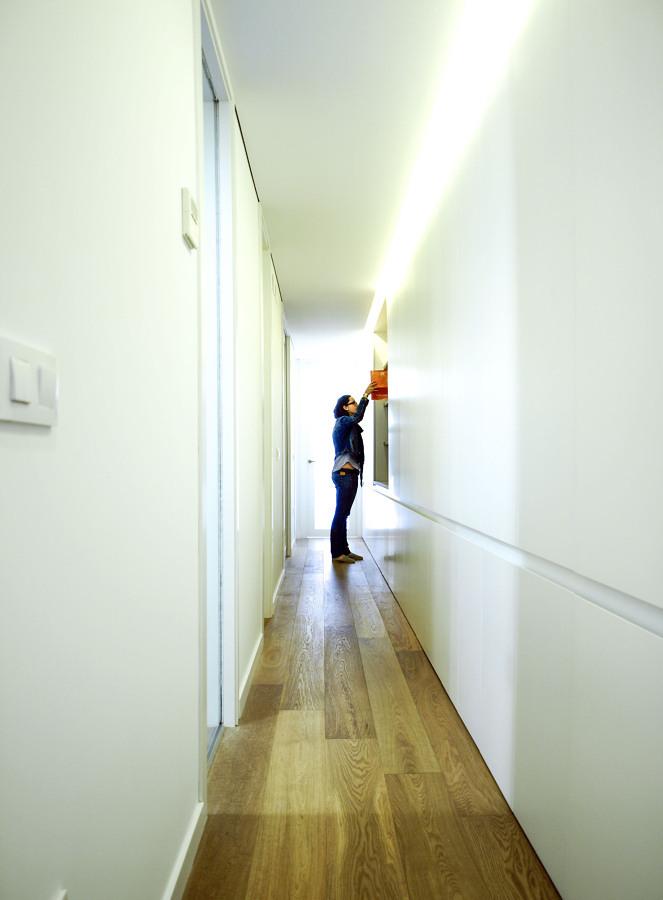 Pasillo con mueble blanco y piso de madera