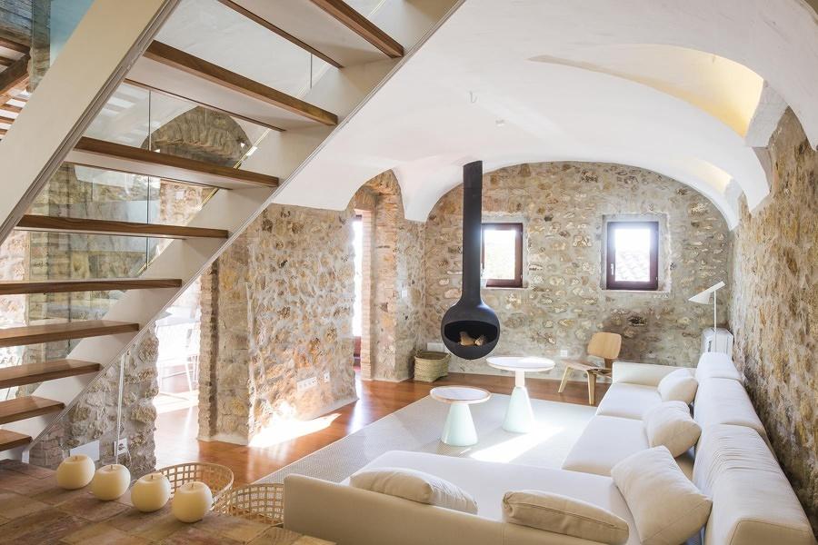 Sala con paredes de piedra y chimenea