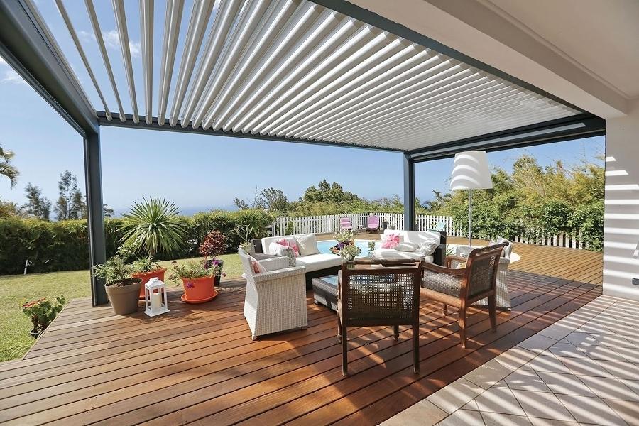 Terraza con piso de madera y pérgola con lamas orientables