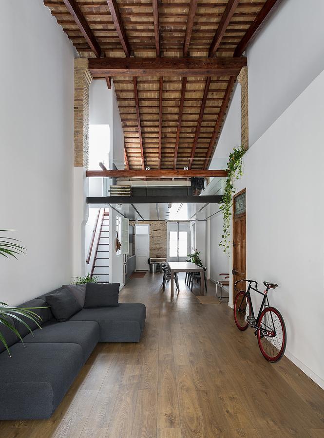 Loft con dos niveles, vigas en el techo y piso de madera