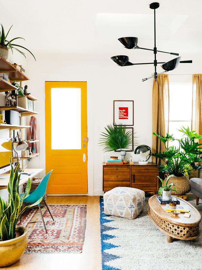 Sala estilo tropical con puerta pintada de color naranja