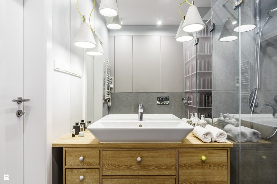 Baño con gabinete de madera y regadera con cancel