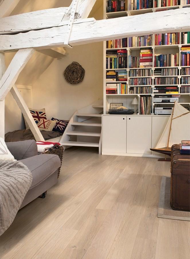 Sala con piso de madera, librero y viga a la vista