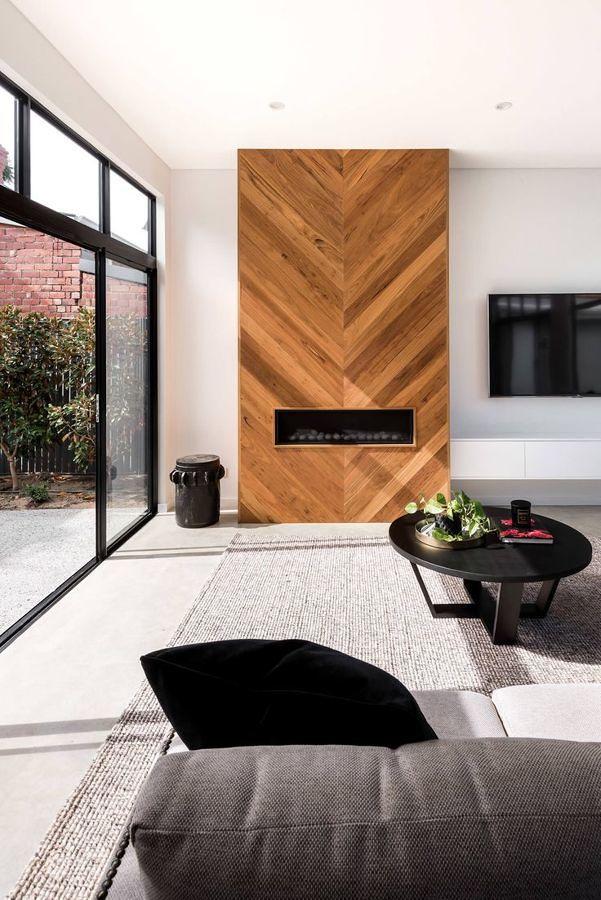 Sala con chimenea y pared de madera