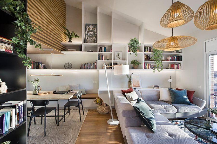 Salón con techo abuhardillado y gran librería de obra.