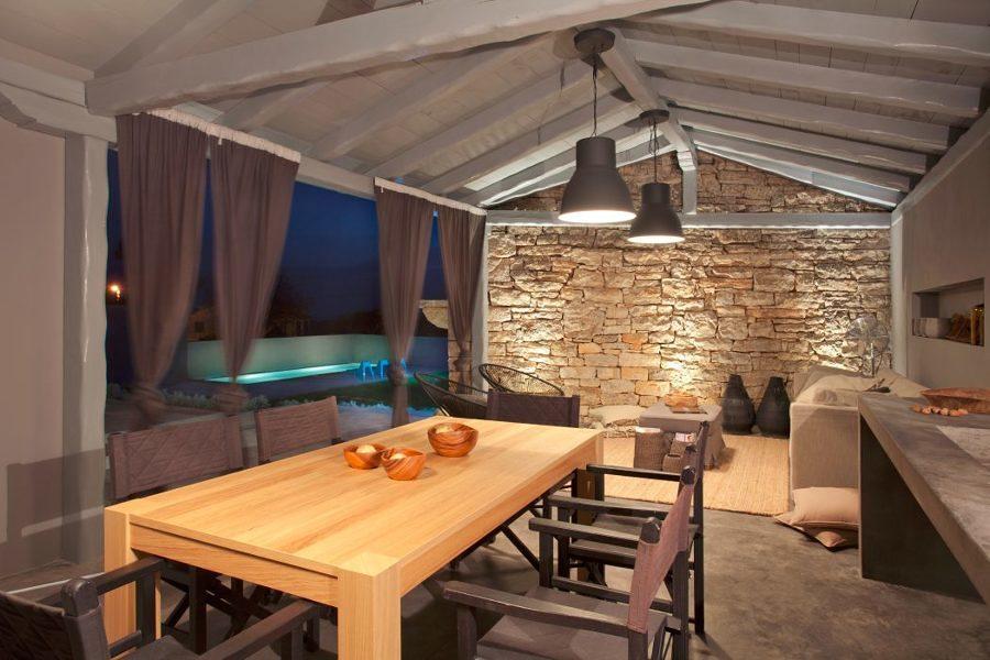 Comedor estilo rústico con piso de microcemento y pared de piedra