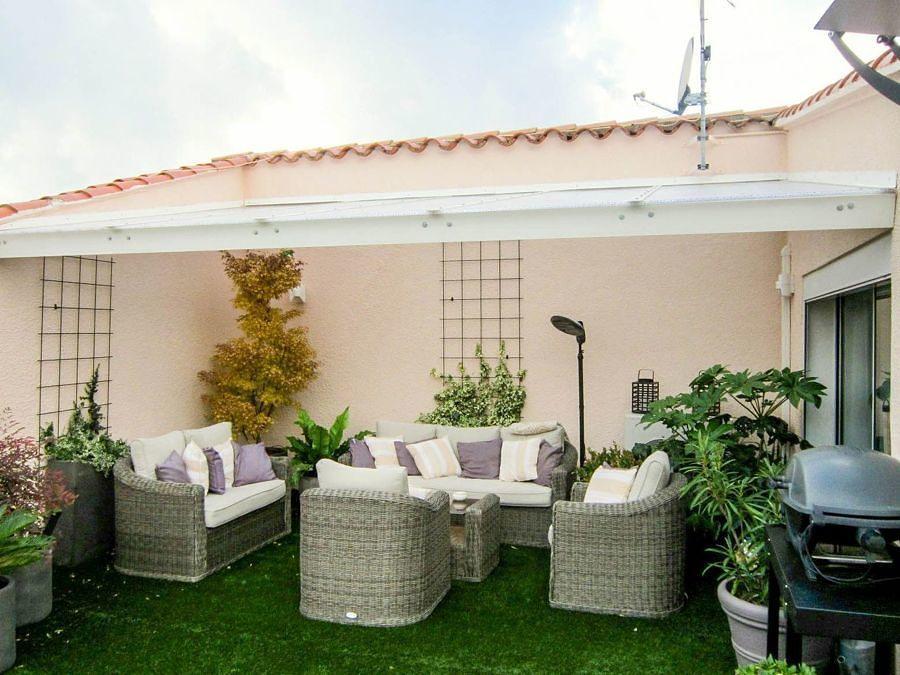 Terraza con techo y pasto en el piso