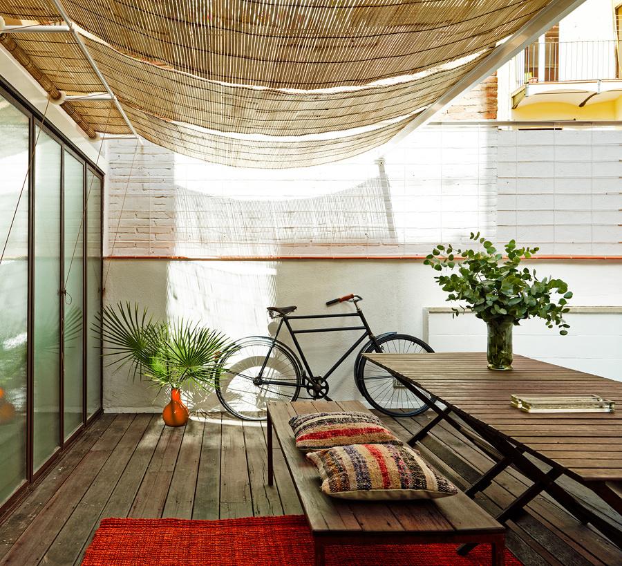 Foto terraza luminosa con piso de madera y toldos de paja for Patio con piso de madera