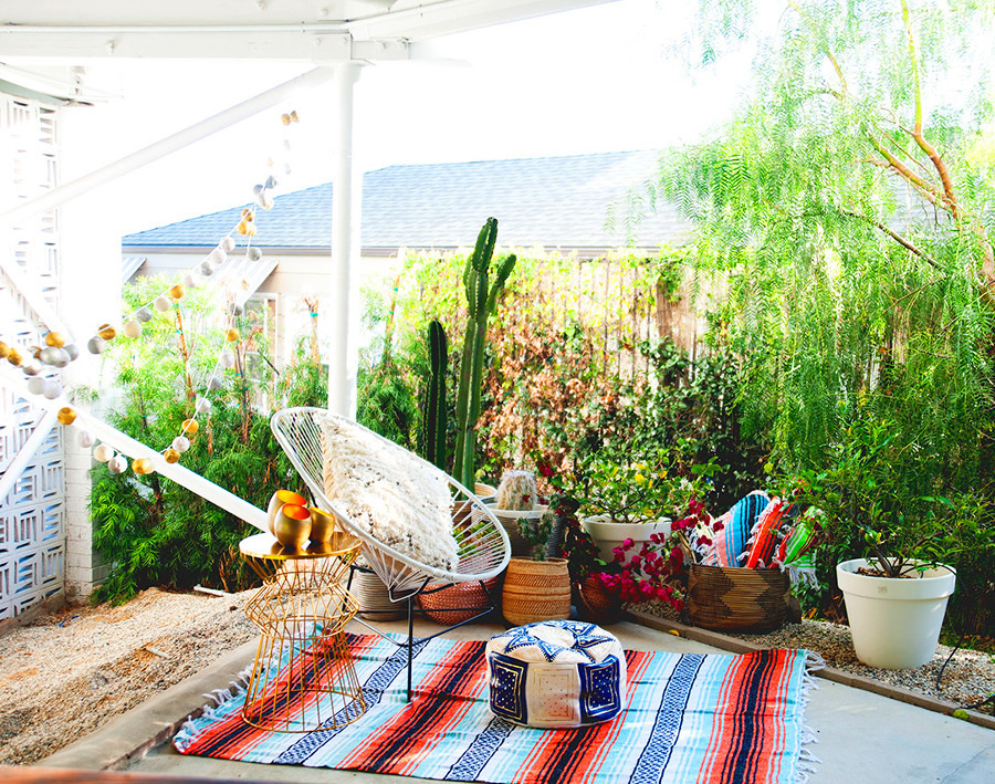 Terraza estilo boho decorada con plantas y alfombras