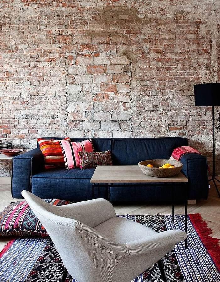 Sala con sofá, textiles y pared de ladrillo visto