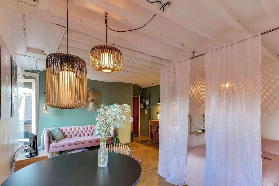 Departamento pequeño con lámparas colgantes y cama separada con cortinas