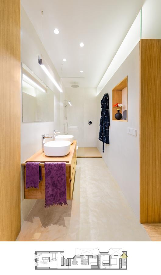 Baño alargado con iluminación y doble lavabo