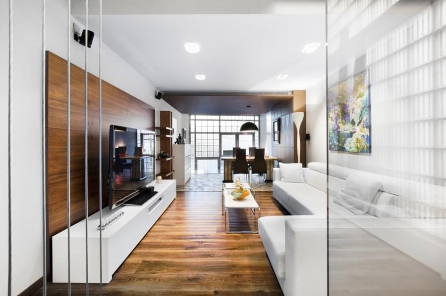 Sala con piso de madera, puertas de vidrio y sofá grande