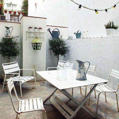 terraza pintada de blanco con muebles de hierro