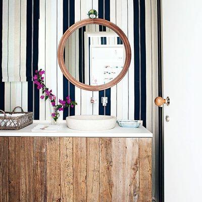 Baño con papel tapiz y mueble a la medida de madera