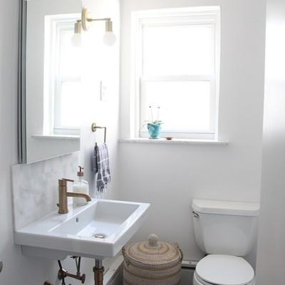 Baño remodelado con paredes en color blanco y piso con azulejos color carbón