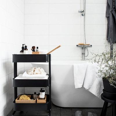 Baño blanco y negro con tina exenta y carrito con ruedas