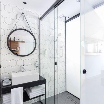 baño con mampara de vidrio y perfil de forja