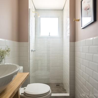 Baño con paredes de azulejo blanco y pintadas de rosa