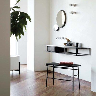 baño con planta, espejo y tocador negro