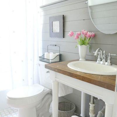 Baño con frisos de madera en la pared