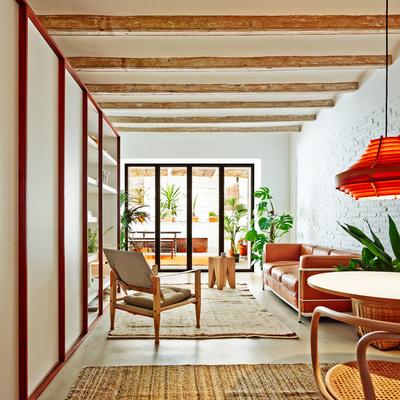 Sala luminosa con pared de ladrillo blanco y vigas en el techo