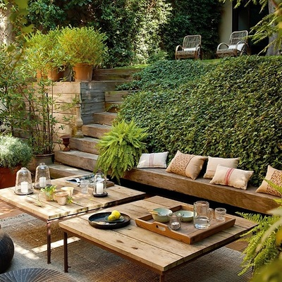 Terraza con mobiliario de madera y jardín