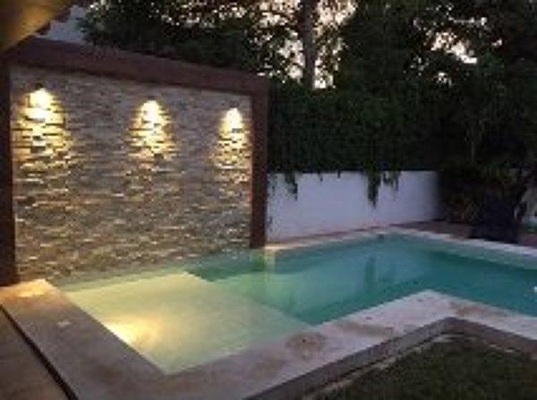 Foto piscina irregular con muro cascada de aquasur for Piscinas pequenas con cascadas