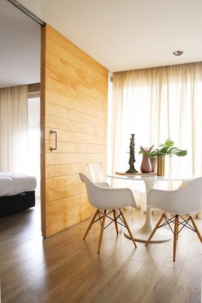 Foto puerta corrediza de madera con riel a la vista for Puerta corrediza de madera para bano
