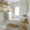 Baño en tonos blancos con estanterías de madera