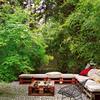 Terraza con bancos de tarima de madera y jardín