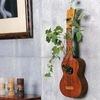 unusual-wall-mounted-bonsai-decor-with-ukulele-vase-in-interior-settings